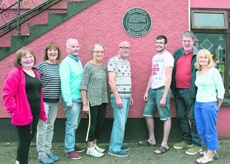 Members of the Courtmacsherry Tidy Towns Committee beneath the plaque at Ruddock