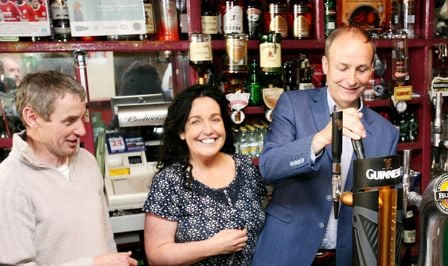 PULL THE OTHER ONE: Fianna Fail leader Mícheál Martintrying his hand at filling a pint at the Horse & Hound pub in Skibbereen last Friday with Cllr Margaret Murphy OMahony and owner Ger Carey.