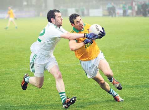 Jerry McCarthy of Dohenys, in possession, is challenged by Aghadas Colm Power in the first round of the County Senior Football Championship.
